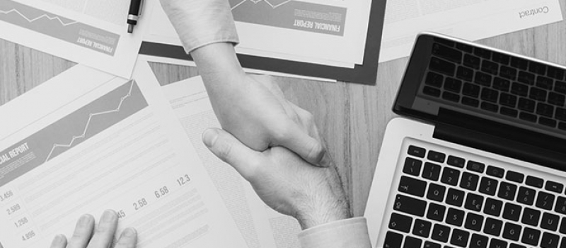 Handshake with paperwork and computer in background - Numerico