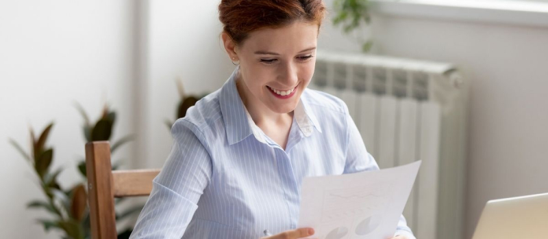Woman looking at pie chart on paper - Numerico
